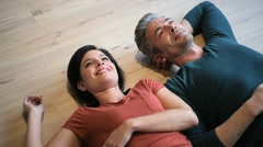 Upper view of couple laying on wooden floor Stock Footage