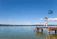 Boy fishing with net in lake Stock Photos