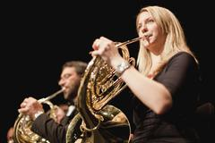French horn players in orchestra Stock Photos
