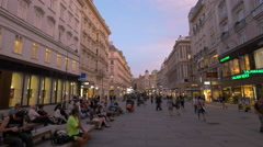 People sitting on benches and walking on Graben in Vienna at sunset Stock Footage