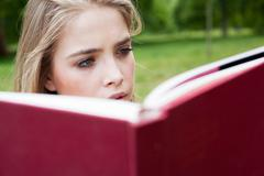 Teenage girl reading in park - stock photo