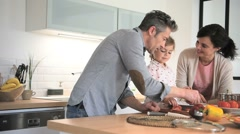 Parents with child cooking together at home Stock Footage