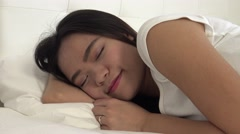 4k, Beautiful asian girl sleeping in bed opening eyes and smiling at camera-Dan Stock Footage