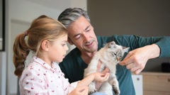 Daddy with little girl cuddling with cat - stock footage