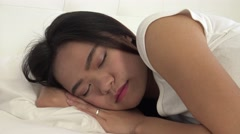4K Attractive sleeping asian woman in bed opening eyes and smiling at camera-Dan Stock Footage