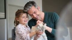 Daddy with little girl cuddling with cat Stock Footage