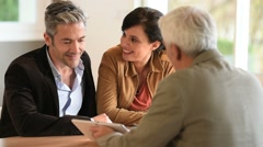 Mature couple signing documents in real-estate agency - stock footage