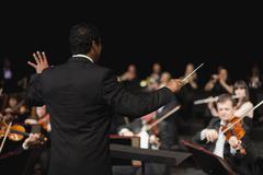 Conductor waving baton over orchestra Stock Photos
