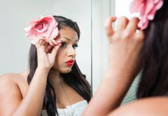 Woman adjusting her makeup in mirror - stock photo