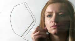 Woman Draws a Pie Chart in Marker on a Pane of Glass - stock footage