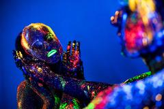 People are colored fluorescent powder. a pair of lovers dancing at a disco. Stock Photos