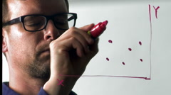 Man Draws a Red Scatter Graph on a Pane of Glass Stock Footage