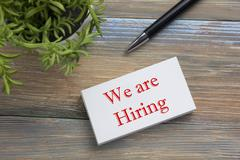 We are Hiring. Office desk table with business card, pen and flower. Top view - stock photo