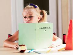 Bored girl doing homework at desk Stock Photos