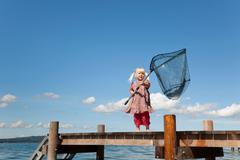 Girl fishing with net in lake Stock Photos