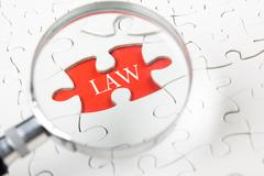 Law concept - Magnifying glass searching missing puzzle peace Stock Photos