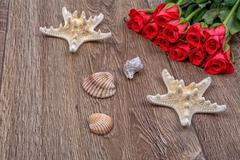 Starfishes, shells and red roses on a wooden background - stock photo