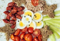 Sliced whole wheat bread with tuna, paprika, sausage, cherry tomatoes, eggs a Stock Photos