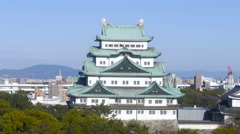 Elevated view of Nagoya Castle in clear, blue skies, and birds flying by Stock Footage