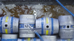 4K Overhead view of barrels of beer being filled with a hose in a brewery Stock Footage