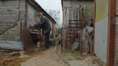 Old Man Pours a Bucket of Feed in Feeder Which is Located in Wall of Old Wooden Stock Footage