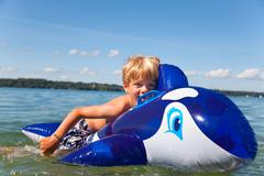 Boy floating in lake with toy whale Kuvituskuvat
