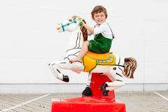 Boy riding mechanical horse outdoors Stock Photos