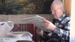 Older Man in Glasses Reading a Newspaper at Table With a Plate of Borsch - stock footage