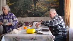 Older Man Wielding Knife and Fork on Plate While a Woman Sits Beside Him on the - stock footage