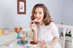 Beautiful woman eating pink heart shaped cookies - stock photo