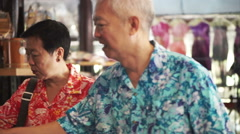 Asian senior tourist walking and shopping for local craft in Thailand - stock footage