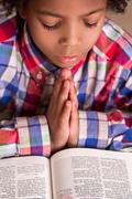 Mulatto boy praying. Stock Photos