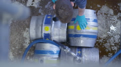 4K Overhead view worker in a brewery preparing barrels of beer for distribution - stock footage