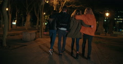 Young happy couples embracing while taking a night walk outside Stock Footage
