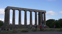 People walking by the National Monument of Scotland on Calton Hill in Edinburgh Stock Footage