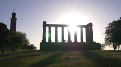 Sun shining behind the National Monument of Scotland in Edinburgh Stock Footage