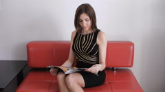 Beautiful young brown haired girl reading a magazine while sitting relaxing on a Stock Footage