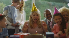 4K Mature lady celebrates her birthday with a cake & happy family group - stock footage