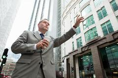 Businessman hailing a cab in city Stock Photos