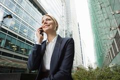 Businesswoman on cellphone amongst office buildings - stock photo