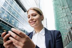 Businesswoman using smartphone amongst office buildings Stock Photos