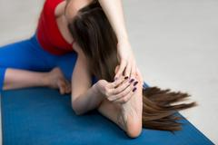 Yoga Indoors: Revolved Head-to-Knee Forward Bend Pose Stock Photos