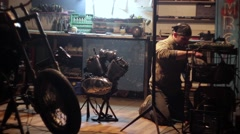 Auto mechanic assembles custom motorcycle in his workshop. - stock footage