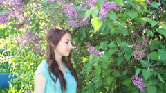 Beautiful woman near lilac tree in spring park Stock Footage