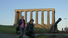 Walking by the cannon and the National Monument of Scotland, Edinburgh Stock Footage