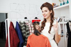 Woman holding dress and bank card in store - stock photo
