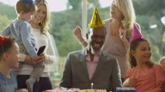 4K Mature man celebrates his birthday with a cake & happy family group - stock footage