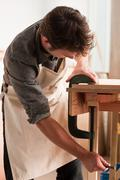 Carpenter adjusting clamp in workshop Stock Photos