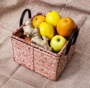Wicker basket with apples, oranges, lemons and ginger - healthy food Stock Photos