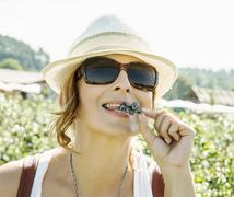 Young caucasian woman eating fresh blueberries, female portrait - stock photo